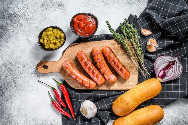 Ингредиенты для разных домашних хот-догов с жареным луком, чили, помидорами, кетчупом, огурцами и колбасой. Premium Фотографии