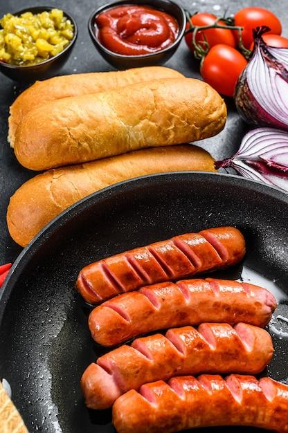 Ингредиенты для приготовления домашних хот-догов. сосиски на сковороде, булочки свежие, горчица, кетчуп, огурцы Premium Фотографии