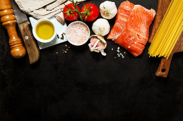Ingredients for making pasta and salmon fillets on a wooden board Premium Photo