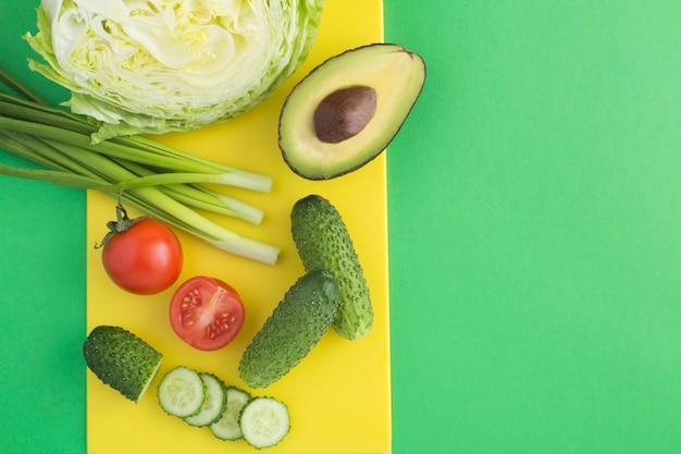 Ингредиенты для салата на желтой разделочной доске Premium Фотографии