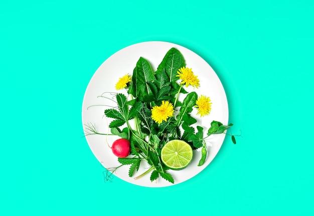 Ingredienti per una fresca insalata verde con denti di leone e fiori commestibili su un piatto Foto Gratuite
