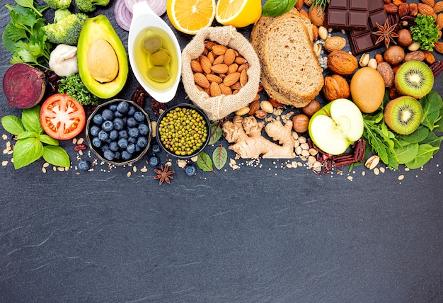 Ingredients for the healthy foods selection set up on dark stone background. Premium Photo