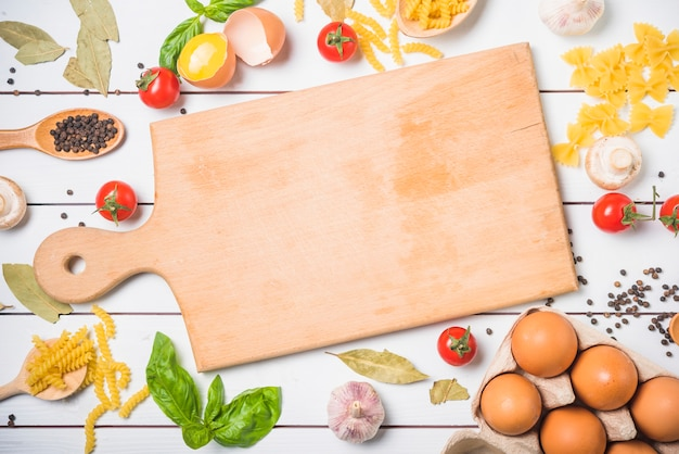 Ingredients for making pasta with chopping board at center Free Photo