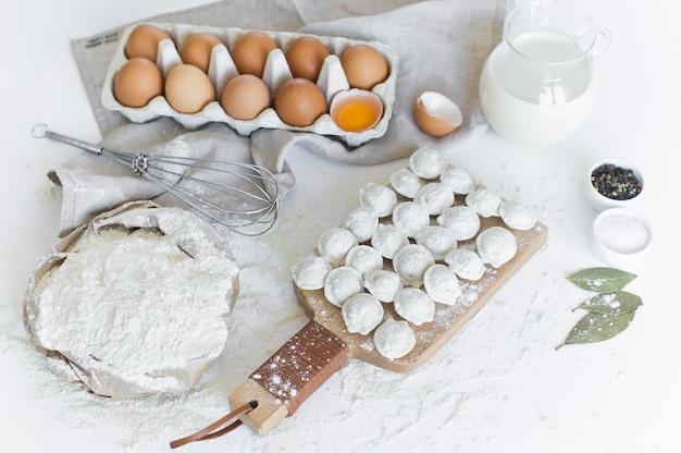 Ingredients for modeling homemade dumplings. eggs, milk, flour, salt, pepper, meat. Premium Photo