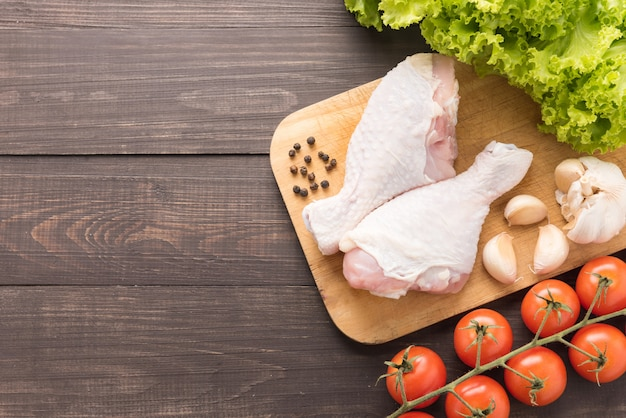 Ingredients and raw chicken leg on cutting board on wooden table Premium Photo