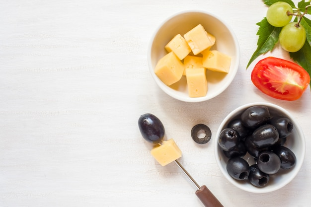 Ingredients for snacks, cheese with olives and tomato, grape on a white table Premium Photo