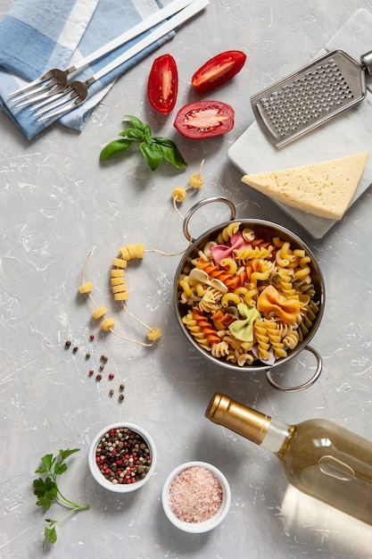 Ingredients for traditional pasta cooking - cheese, tomatoes, condiments. Premium Photo