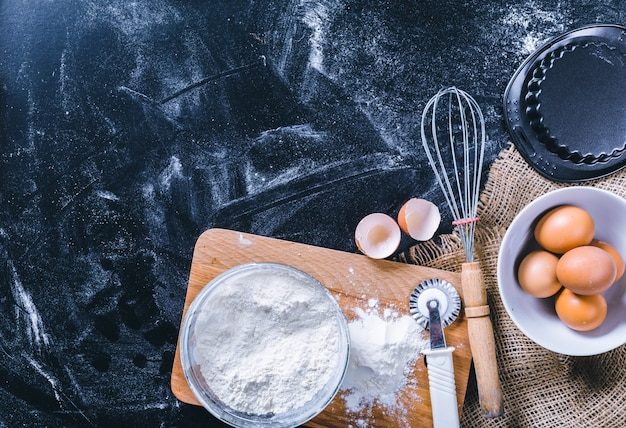 Ingredients and utensil for baking on the black board, top view Premium Photo