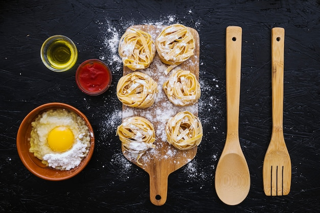 Ingredients and utensils near pasta with flour Free Photo