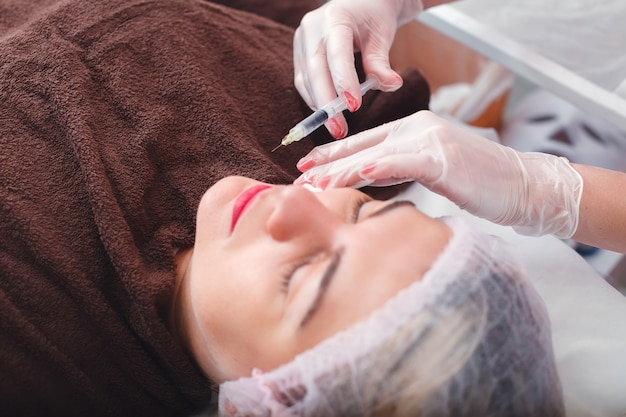 Injection syringe in the woman's face. Premium Photo