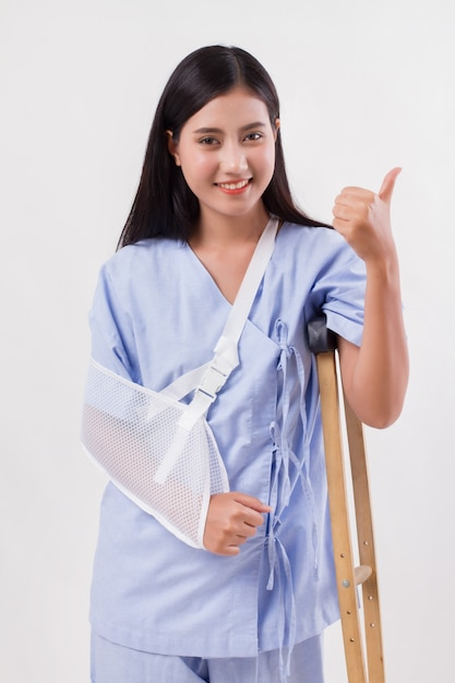 Injured woman patient pointing thumb up gesture away Premium Photo