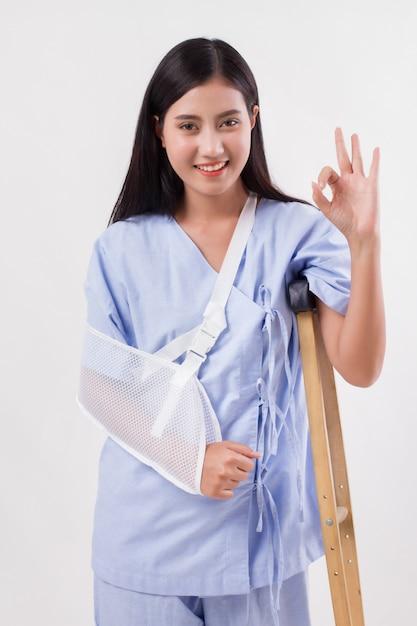 Injured woman patient pointing up ok hand gesture Premium Photo