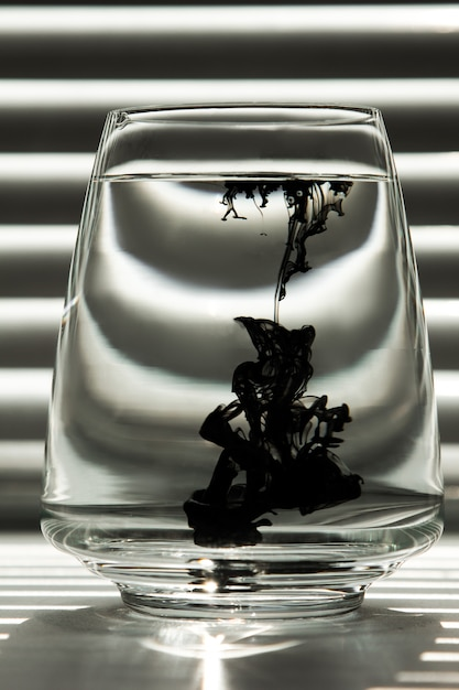 Ink in a transparent glass cup with clear water against the backdrop of a striped screen Premium Photo
