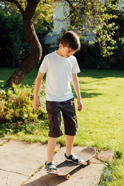 Innocent boy playing skateboard in the park Free Photo