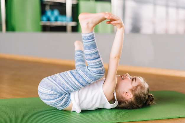Innocent girl child practicing yoga in fitness center Free Photo