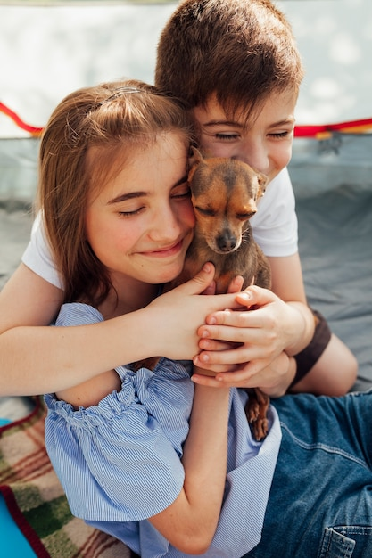Innocent smiling sibling loving their pet in tent Free Photo