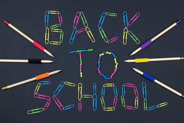 Inscription back to school on the background blackboard made of colorful paper clips Premium Photo