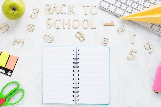 Inscription back to school and stationary on table Free Photo