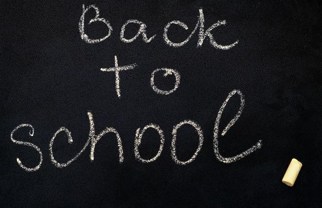 黒い黒板に学校に戻る碑文をクローズアップ。 無料写真