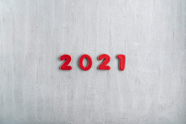 灰色の背景にジンジャーブレッドから赤い数字2021の碑文。 2021年の新年、コピースペース。 Premium写真