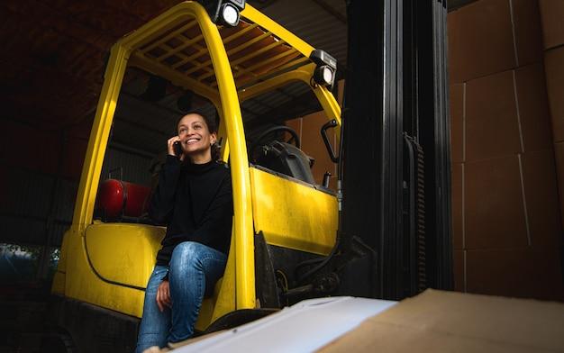 На складе молодая женщина сидит на подножке желтого вилочного погрузчика и разговаривает по телефону. Premium Фотографии
