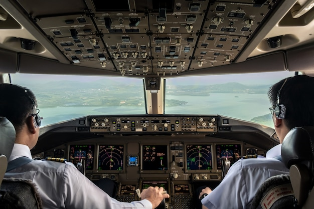 Inside cockpit of commercial airplane while fly approaching the runway. Premium Photo