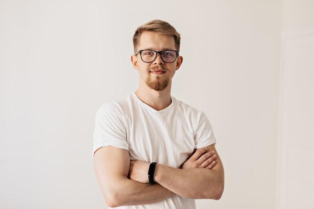 All'interno ritratto di giovane fiducioso in vestiti bianchi in posa con un sorriso affascinante sopra la parete isolata. Foto Gratuite