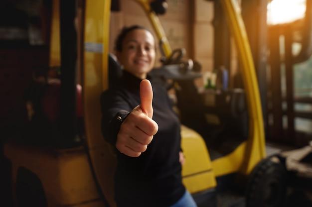 Внутри склада молодая женщина стоит перед желтым вилочным погрузчиком и показывает палец вверх. Premium Фотографии