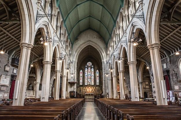 Vista interna di una chiesa con icone religiose alle finestre e archi in pietra Foto Gratuite