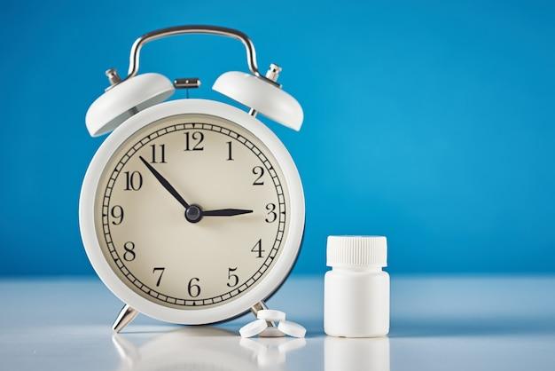 不眠症の問題の概念。目覚まし時計と青色の背景に丸薬 Premium写真