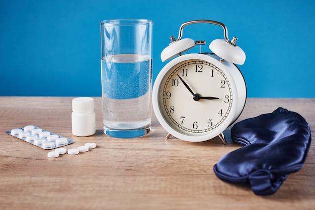 不眠症の問題の概念。目覚まし時計、ガラスの水と青色の背景に丸薬 Premium写真