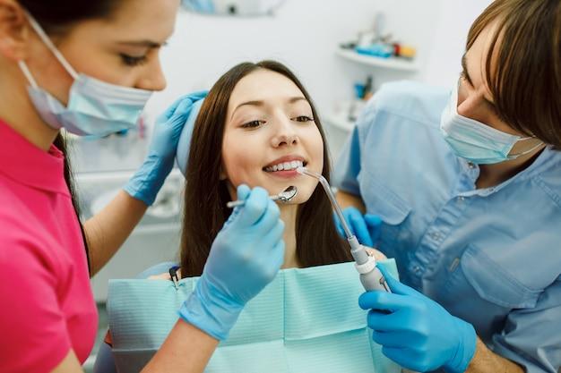 Ispezione dei denti della donna con l'aiuto di uno specchio. Foto Gratuite
