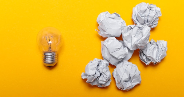 Inspiration concept crumpled paper and light bulb metaphor for good idea. white crumpled paper and light bulb on yellow background, flat lay. Premium Photo