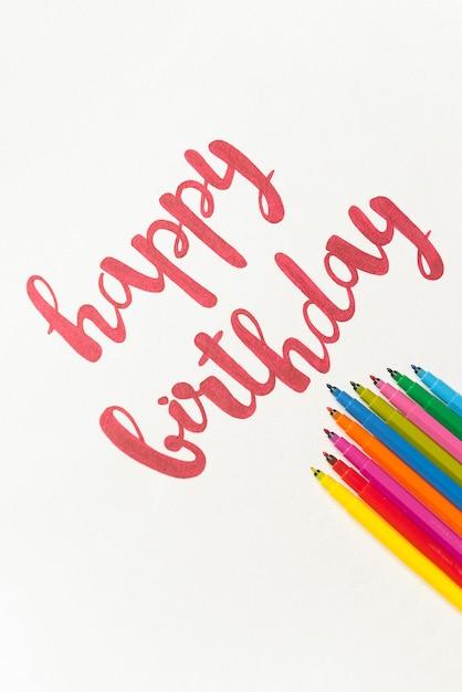 Вдохновляющие фразы «с днем рождения» для поздравительных открыток и плакатов, рисунок с красным маркером на белой бумаге. вид сверху надписи, куча разноцветных маркеров Бесплатные Фотографии