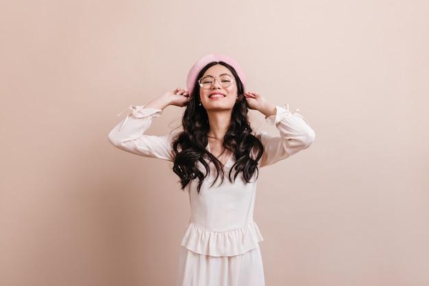 베레모에 포즈를 취하는 영감을받은 중국 아가씨. 유행 복장에 Blithesome 아시아 여자의 전면 모습. 무료 사진