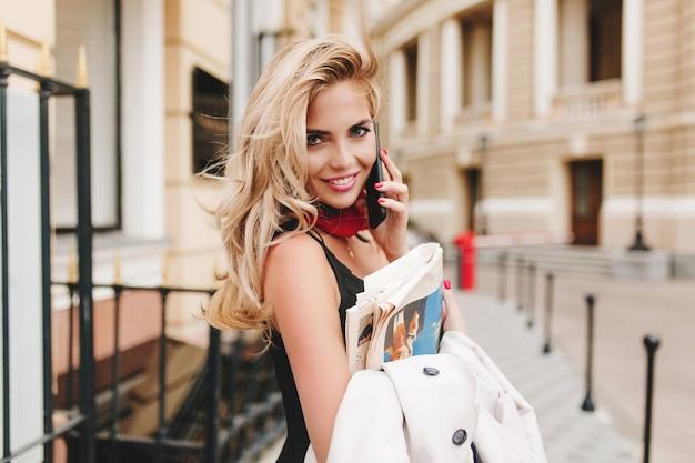 Вдохновленная кудрявая женщина, держащая куртку, смеется, разговаривая с кем-то по телефону Бесплатные Фотографии