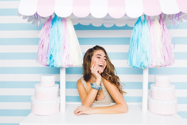 Inspired cute long-haired girl in trendy blue accessories sitting behind counter with desserts on striped wall. charming female seller happy laughing posing in candy shop with eyes closed. Free Photo