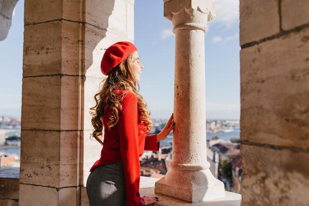 石の柱の近くに立って街の景色を楽しむ巻き毛の髪型を持つインスピレーションを得たフランスの女の子 無料写真