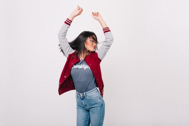 Вдохновленная девушка носит стильную спортивную куртку, прыгает с поднятыми руками. возбужденная студентка рада танцевать, потому что получила высокую оценку. Бесплатные Фотографии