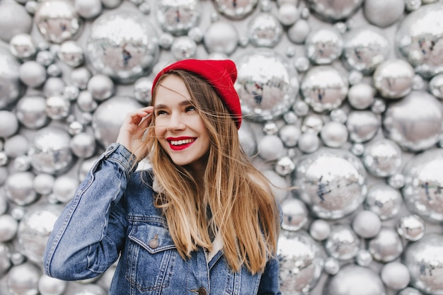 Inspired girl with brown straight hair looking away with smile during photoshoot with party accessories. photo of lovely european woman in red hat standing near disco balls. Free Photo