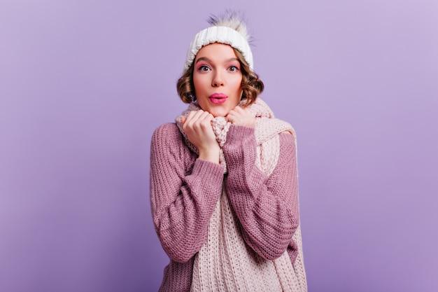 ピンクの化粧と紫色の壁にポーズをとって驚いた笑顔を持つインスピレーションを得た女の子。幸せを表現する帽子とスカーフのかわいい若い女性。 無料写真
