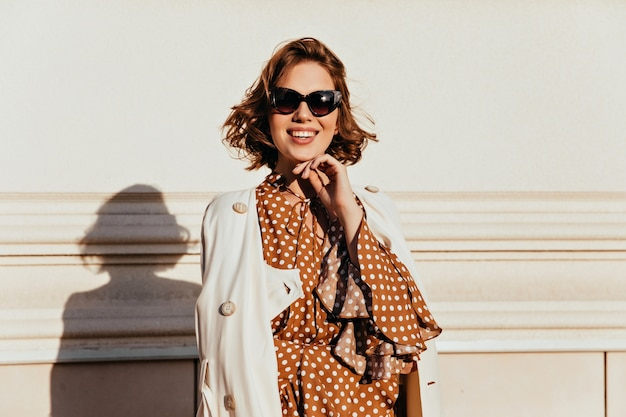 壁の横に立っているサングラスのインスピレーションを得たスタイリッシュな女性。茶色の髪の明るい女の子を笑う屋外ショット。 無料写真
