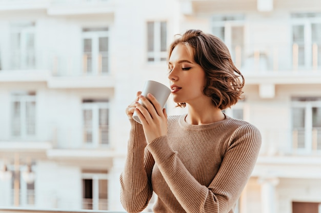 Inspired white lady with curly hairstyle drinking tea. gorgeous young woman enjoying coffee in cold autumn morning. Free Photo