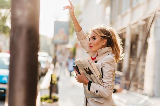 刺激的な若いビジネスウーマンが職場に急いで通りでタクシーに乗る 無料写真