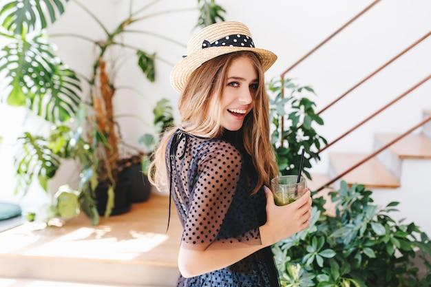 肩越しに見て、冷たい飲み物のグラスを持って笑っている長い光沢のある髪を持つインスピレーションを得た若い女性 無料写真