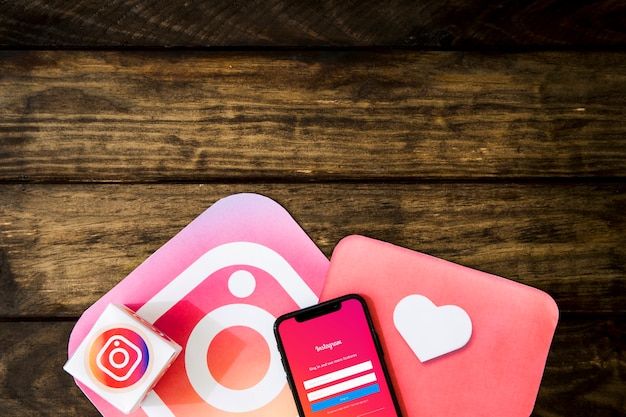 Instagram interface with mobile phone on wooden table Free Photo
