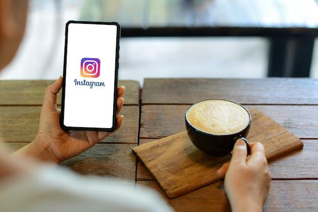 スマートフォンのディスプレイにinstagramのアプリケーションを示すiphoneスマートフォンを保持している若い女性 Premium写真