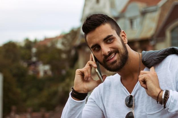 屋外で電話で話すハンサムな男。革製のジャケット、サングラス、ひげを持つ男。 instagramエフェクト 無料写真