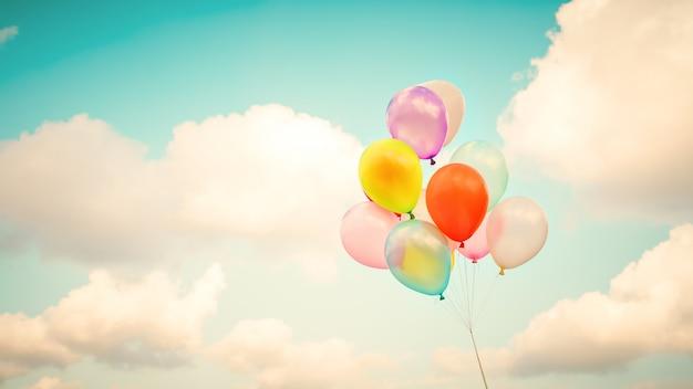 ヴィンテージの多色風船は青い空にレトロなinstagramフィルター効果で行われます。夏とバレンタイン、結婚式の新婚旅行の概念で愛の背景のためのアイデア。 Premium写真