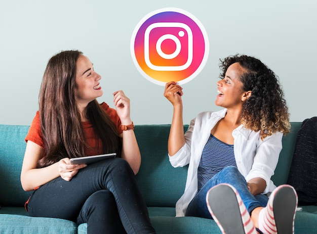 Instagramのアイコンを示す若い女性 Premium写真